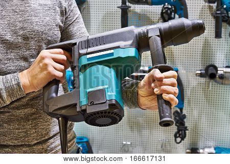 The hammer drill in man's hands closeup