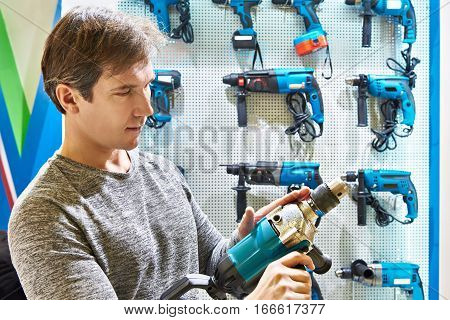 Man Shopping For Hammer Drill In Hardware Store