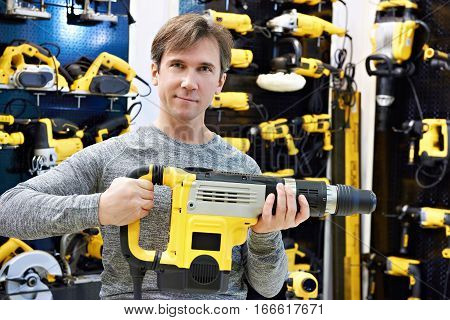 Man With Hammer Drill In Hardware Store
