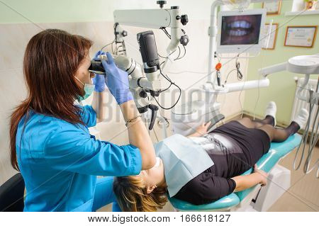 Female Dentist Working With Microscope At Modern Dentist Clinic