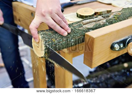 Man Sawing Wood Handsaw On Carpentry Table