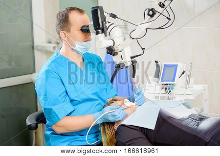 Male Dentist Working With Microscope At Modern Dentist Clinic