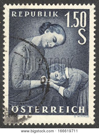 MOSCOW RUSSIA - CIRCA DECEMBER 2016: a post stamp printed in AUSTRIA shows a mother and a child dedicated to the Mother's Day circa 1958