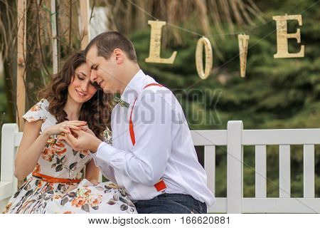 Young Lovely Couple Playing And Laughing Near A Love Sign, Engagement Photo