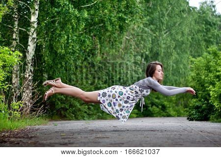 Young Brunette Girl In Colorful Dress Levitating In The Park. Green Trees Lit With Bright Summer Sun