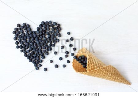 blueberries are strewed at desk of the waffle cone top view / heart of berries to the holiday