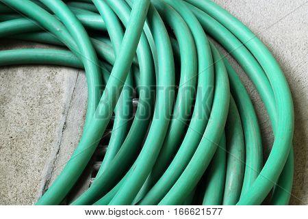 Green Garden Water Hose On Cement Floor