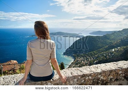 Young brunette girl sitting on the stone looking at the scenic panoramic view of Eze Sur Mer. Cote de azure. Bright sunny summer day in Europe.