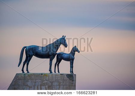 Statue of mare and foal on the sky with clouds