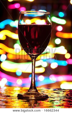 Wine glass with blured motion lights in the background