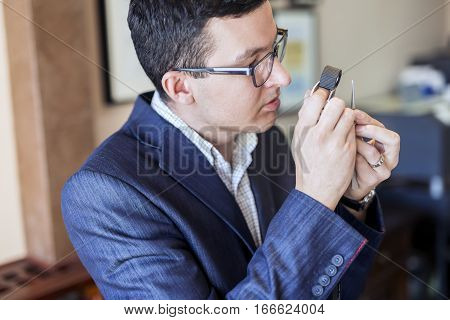 Jeweler looking at diamond through loupe to inspect it