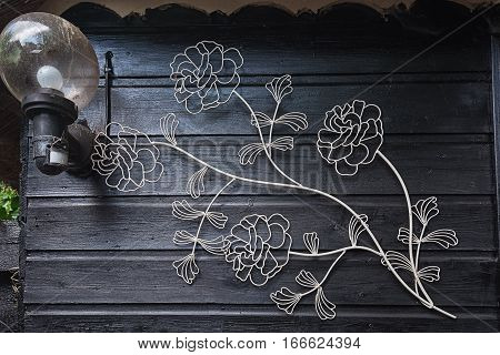 Wrought iron flowers on the wall next to the lantern.