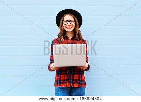 Fashion Young Smiling Woman Holding Laptop Computer In City, Wearing Black Hat, Red Checkered Shirt
