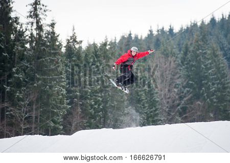 Male Snowboarder Jumping Over The Slope In Winter Day