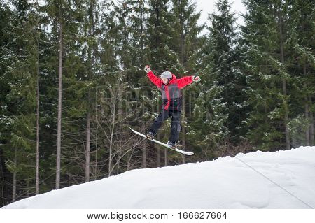 Male Boarder On The Snowboard Jumping Over The Slope