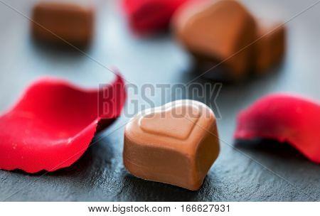 Heart shaped pralines and rose petals on black slate