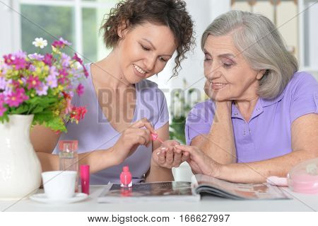 daughter  making manicure to her mother, painting nails
