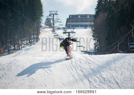 Female Boarder On The Snowboard After Jumping Over The Slope