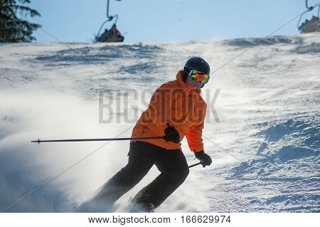 Male Skier Skiing Downhill At Ski Resort Against Ski-lift