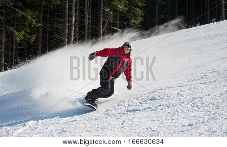 Male Snowboarder Slides Down From The Mountain