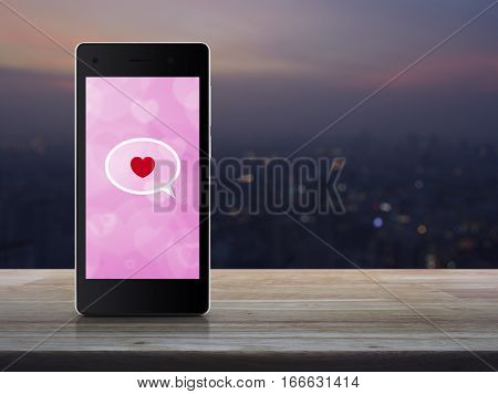 Love message on modern smartphone screen on wooden table over blur cityscape on warm light sundown Internet online connection Valentines day concept