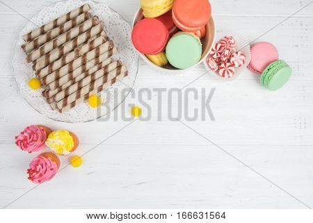 Colorful Candy, Cupcakes, Macaroons, Wafer Rolls On White Wooden Background