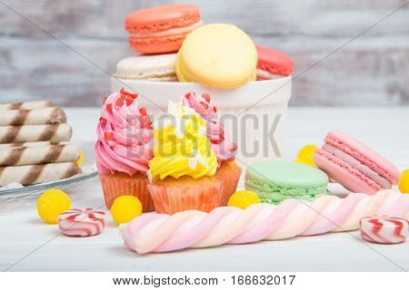 Colored Sweets Closeup: Cupcakes, Macaroons And Candy On Wooden Background