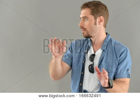 Portrait of a young man gesticulating against gray background