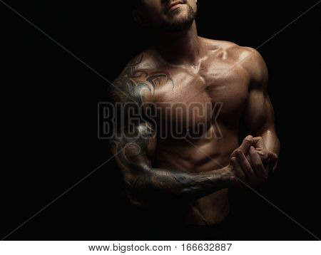 Strong athletic man, bodybuilder. Unrecognizable, no face portrait. Naked torso, muscular body. Strong chest and shoulder muscles. Studio shot on black background, low key. Bodybuilding concept