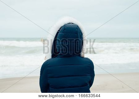 Woman In A Blue Winter Jacket With A Hood Stands On The Winter Beach And Looking At Sea