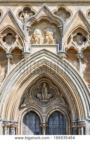 Wells United Kingdom - August 6 2016: Sculpture of the Virgin and Christ Child above the west door of Wells cathedral.