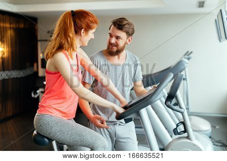 Personal young trainer giving instructions in gym