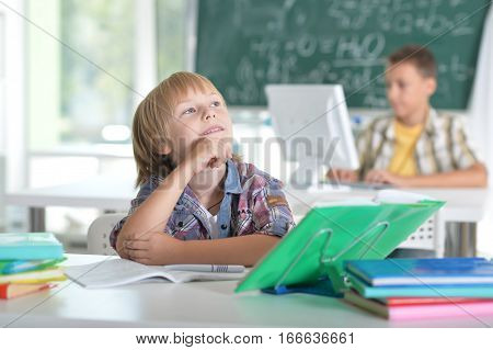 smiling little boy in the classroom, his classmate on background
