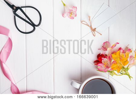 Flowers, coffee and other objects on white wooden table, top view.
