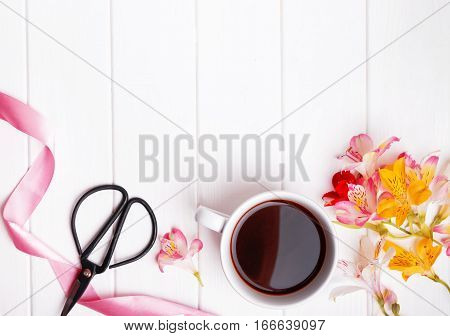 Flowers, coffee, scissors and pink ribbon on the white table, top view