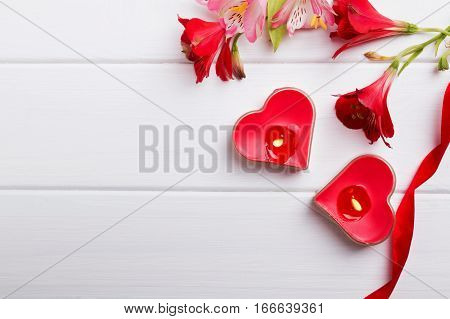Two heart shaped candles and flowers on the white wooden table. Valentine's day template.