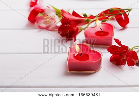 Two heart shaped candles and alstromeria flowers on the white table, close-up. Valentine's day concept.