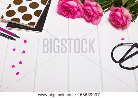 Beautiful objects on the white table: pink roses, paper hearts and notepads