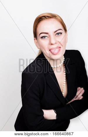 Attractive and energetic business woman in a suit on a naked body showing tongue.