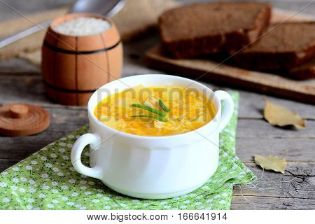 Delicious rice soup with chicken, potatoes, green onions and carrots in a bowl. Bread slices, green napkin, small decorative barrel with raw rice on wooden table. Quick and easy soup recipe. Closeup