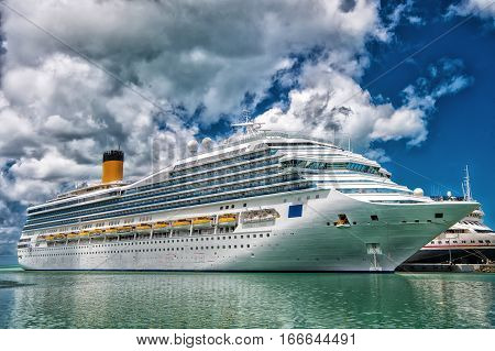 Large luxury cruise ship  on sea water and cloudy sky background docked at port of st.Johns Antigua