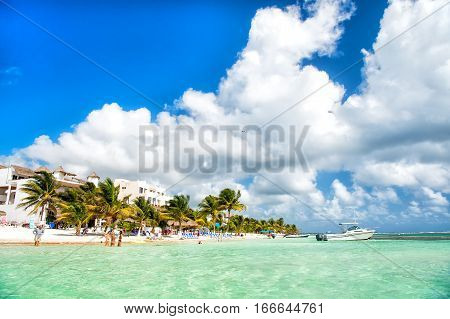Costa Maya Mexico-February 2 2017: tropical summer vacation beach with sea or ocean water green palm trees blue sky with people and umbrellas on sand coast sunny day outdoor at Costa Maya Mexico