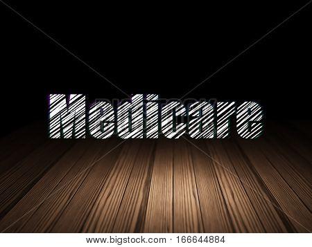 Medicine concept: Glowing text Medicare in grunge dark room with Wooden Floor, black background