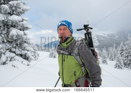 Dreaming man with backpack goes through snow covered pine forest in the winter mountains after a snowstorm.