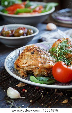 Roasted chicken and vegetables on dark wooden background