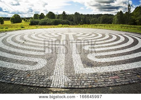 Gothic labyrinth from black and white cobble-stones in the field. Europe. Letonia. Symbol of a new way clarification
