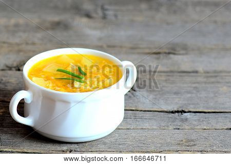 Rice soup. Homemade rice soup with meat, potatoes and carrots in a bowl isolated on old wooden background with copy space for text. Dinner or lunch recipe. Closeup