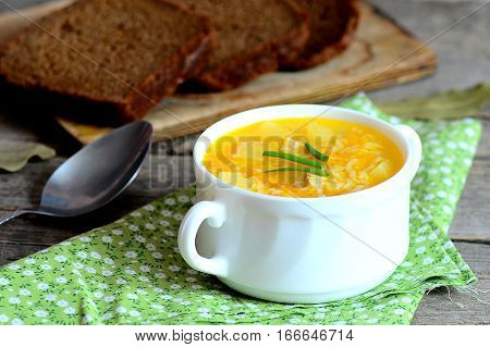 Easy rice soup. Home rice soup with meat, potatoes and carrots in a bowl. Bread pieces, spoon, green napkin on old wooden table. Dinner or lunch dish. Closeup