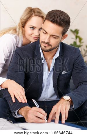 Blonde secretary seducing rich businessman at work while signing contracts