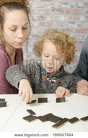 happy family mother and child playing dominos
